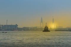 Коммерчески плавание корабля на реке около моста во время захода солнца Стоковая Фотография