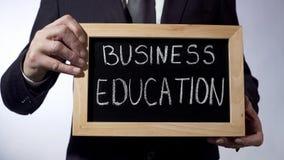 Коммерческое образование написанное на классн классном, бизнесмене держит знак, будущее Стоковые Изображения