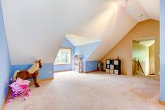 Комната голубого чердака живущая с игрушками и игровой площадкой Стоковое фото RF