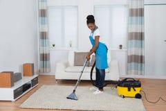 Комната женщины очищая живущая стоковое фото