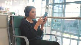 Комната залы аэропорта ждать для полета самолетом молодой счастливый девочка-подросток в наушниках слушая музыку дальше сток-видео