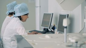 Комната лаборатории больницы с анализировать оборудование и медицинский персонал в ем акции видеоматериалы