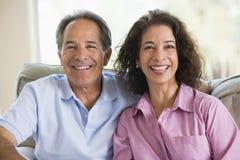 комната пар смеясь над живя ослабляя Стоковая Фотография