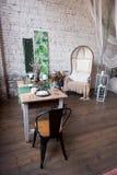 Комната современной просторной квартиры живущая с высокими потолками, софой, пустой белой кирпичной стеной, деревянным полом, акс стоковое фото