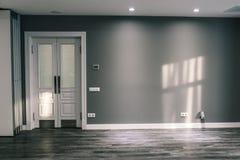 Комната с серой стеной и белой дверью Стеклянная дверь с выпушкой На слепимости солнца пола и стены красит гармоничным конструкто стоковые фото