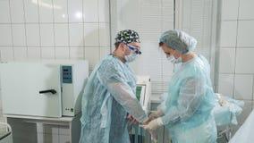 Комната хирургии в больнице Доктора подготавливают для хирургии, помощи медсестры хирург получает в деятельность задний стиль при сток-видео