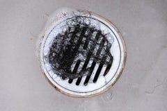 Комок волос в стоке ванны пока принимающ ливень стоковое фото rf