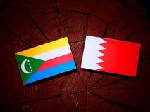 Коморские Острова сигнализируют с бахрейнским флагом на пне дерева Стоковое фото RF