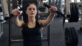 Комод женщины нагнетая muscles на специальном оборудовании в спортзале спорта видеоматериал