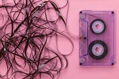 Компактная магнитофонная кассета на розовой предпосылке с запутанной лентой Стоковые Изображения