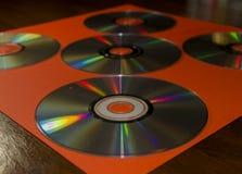 Компактные диски на оранжевой бумаге конструкции Стоковое Фото