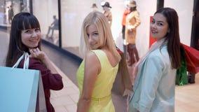 Компания девушек shopaholics идет через мол во время покупки на магазинах моды в сезоне скидок и продаж акции видеоматериалы