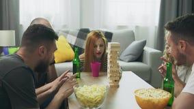 Компания друзей играет деревянную башню в уютной живущей комнате акции видеоматериалы
