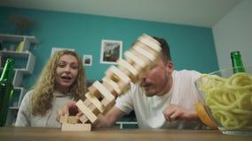 Компания друзей играет деревянную башню в уютной живущей комнате видеоматериал