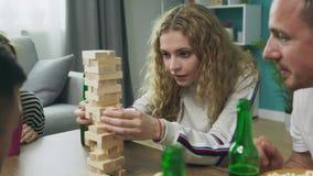 Компания друзей играет деревянную башню в уютной живущей комнате сток-видео