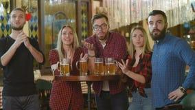 Компания друзей - молодые парни и девушки держа стекла пива, наблюдая футбола, смеясь и усмехаясь на баре сток-видео