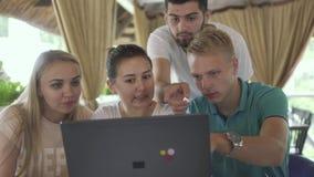 Компания друзей смотря экран компьтер-книжки в кафе сток-видео