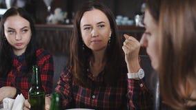 Компания жизнерадостных девушек в ресторане Девушки имея пиво потехи выпивая и есть пиццу Изображения девушек  акции видеоматериалы