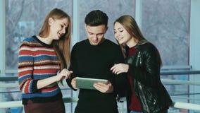 Компания жизнерадостного молодые люди использует устройство таблетки экрана касания видеоматериал