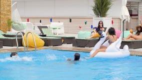 Компания людей плавая в бассейне счастливая группа людей делает брызгает воды в замедленном движении и потехе иметь акции видеоматериалы