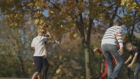 Компания мальчиков играет outdoors Дети бросают листья на одине другого сток-видео