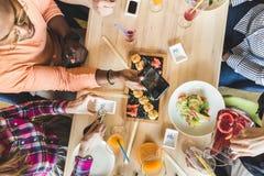 Компания многокультурных молодых людей компании в кафе есть крены суш, выпивая напитки имея потеху стоковая фотография rf
