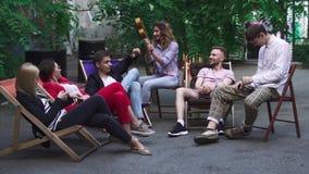 Компания молодые люди отдыхает на зоне лета в кафе видеоматериал