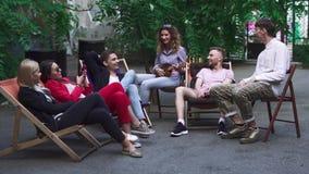Компания молодые люди отдыхает на зоне лета в кафе акции видеоматериалы