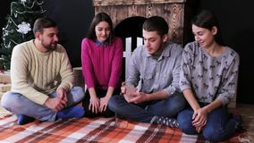 Компания молодые люди сидя на поле и играя карточках дома, тратит время совместно сток-видео
