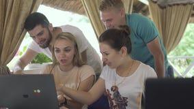 Компания молодые люди смотрит экран компьтер-книжки и имеет обсуждение в кафе акции видеоматериалы