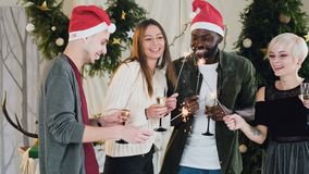 Компания молодых красивых людей различных гонок имеет потеху танцуя рядом с рождественской елкой отпразднуйте друзей сток-видео