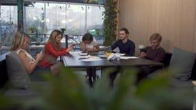 Компания молодых людей сидя на таблице зала заседаний правления на предпосылке окна обозревая оживленную улицу печатая и акции видеоматериалы