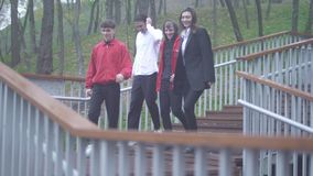 Компания 4 прогулок людей вниз в друзьях парка тратит приятельство времени на открытом воздухе совместно акции видеоматериалы