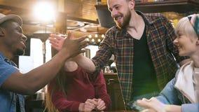 Компания multi этнических друзей используя умный телефон в баре, паб когда их мужские друзья приходя к ним сток-видео