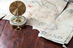 Компас золота морской на старой ретро карте пирата с крестом красного знака Поддельная карта сокровища на деревянном столе Стоковое Изображение RF