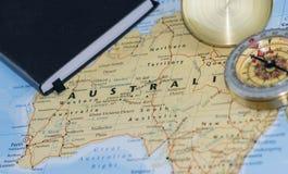 Компас на конце вверх по карте указывая на Австралию и планируя назначение перемещения с примечаниями путешественника в фото стоковая фотография rf