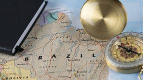 Компас на конце вверх по карте указывая на Бразилию и планируя назначение перемещения стоковые изображения rf