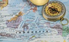 Компас на конце вверх по карте указывая на Индонезию и планируя назначение перемещения стоковые фото