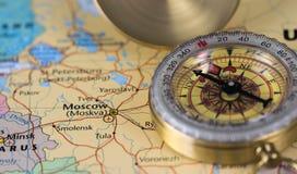 Компас на конце вверх по карте указывая на Москву и планируя назначение перемещения стоковое фото