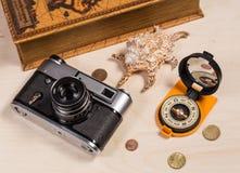Компас, ретро photocamera, cockleshell и монетки на деревянном ба Стоковые Фотографии RF