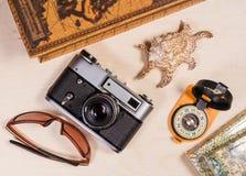 Компас, ретро photocamera, cockleshell и солнечные очки на древесине Стоковое Фото