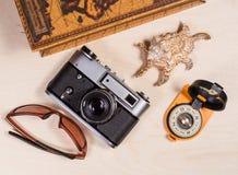 Компас, ретро photocamera, cockleshell и солнечные очки на древесине Стоковые Фотографии RF