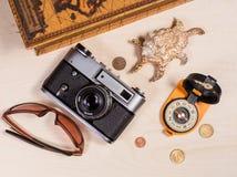 Компас, ретро photocamera, cockleshell, солнечные очки и монетки дальше Стоковая Фотография RF