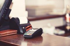 Компенсация с кредитной карточкой Красная кредитная карточка введенная в машину EDC стоковые изображения