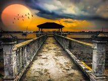 Комплекты Солнця над пристанью рыбной ловли Стоковые Изображения RF