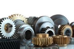 Комплекты шестерней, cogwheels сделанных из стали и изолированной латуни на белой предпосылке с отражением тени Шестерни спиральн Стоковое Фото