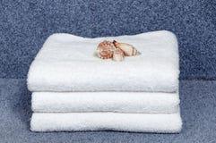 Комплект белых полотенец гостиницы сложил на голубой предпосылке штабелировано Стоковые Фото