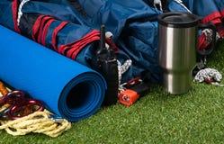 Комплект вещей путешественника туристских лежа на зеленой траве Стоковое Фото