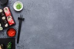 Комплект взгляд сверху maki и кренов суш на деревенской предпосылке серого цвета и сезама Стоковая Фотография RF