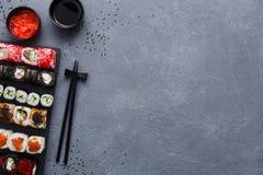 Комплект взгляд сверху maki и кренов суш на деревенской предпосылке серого цвета и сезама Стоковые Фото